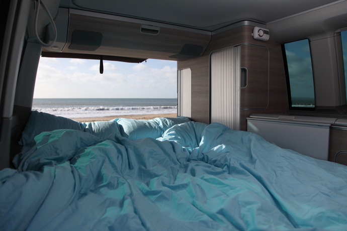 Forget London with a view from a VW California campervan hire sleeping area looking out towards the sea