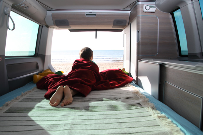 Young boy laying in sleeping area of VW campervan