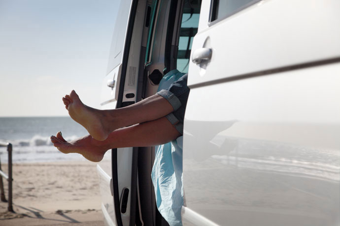 Bare feet show through sliding door of VW campervan parked at the beach