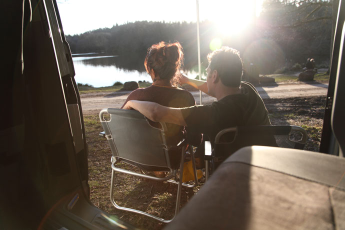 Couple sat on camping chairs outside a campervan parked near a lake
